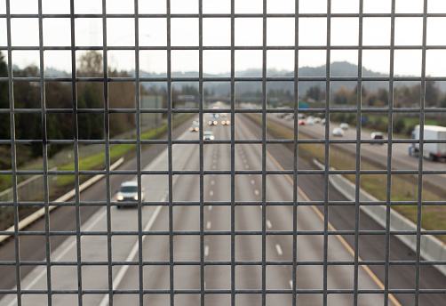 Overlooking a highway behind a high safety fence on a overpass.