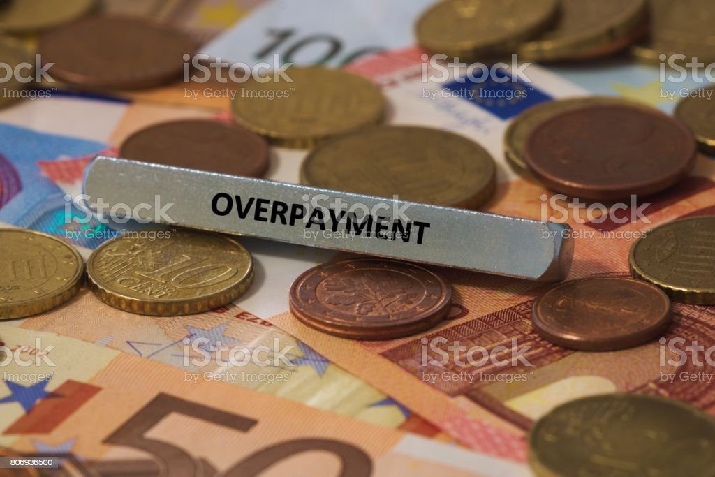 overpayment - the word was printed on a metal bar. the metal bar was placed on several banknotes stock photo