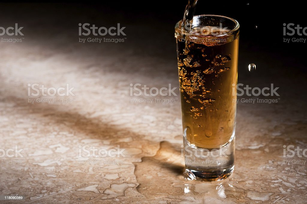Over-pouring a shot of whiskey royalty-free stock photo