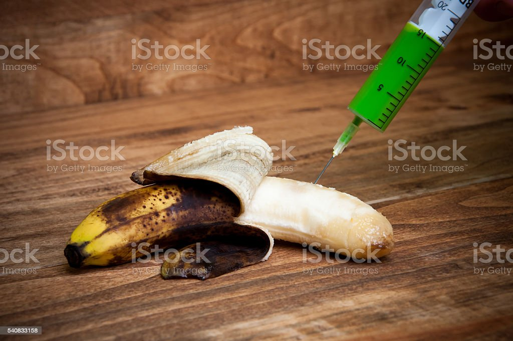 Overripe banana being injected with a syringe stock photo