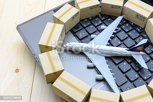 Overseas freight / international delivery or global logistics concept : White model airplane (heading left) lands on a laptop computer keyboard, encircled with light brown paper boxes or goods cartons
