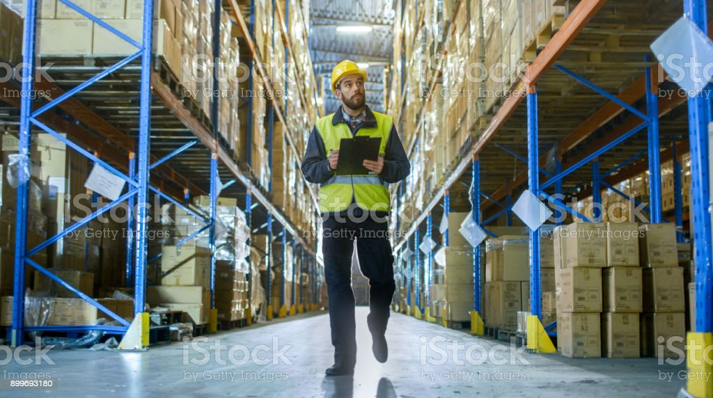 Overseer Wearing Hard Hat with Tablet Computer Counts Merchandise in Warehouse. He Walks Through Rows of Storage Racks with Merchandise. stock photo