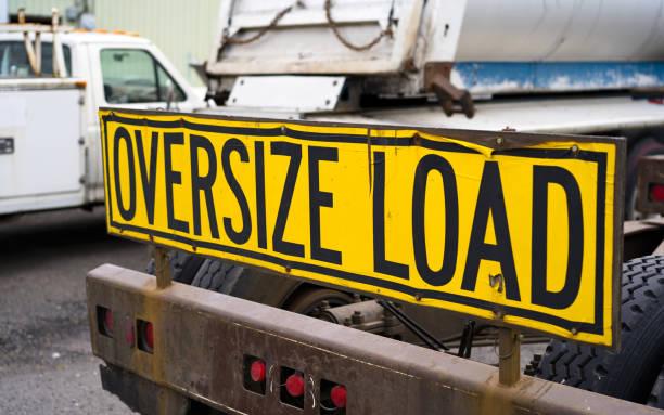 oversize belasting teken op de achterkant van de grote tuig semi vrachtwagen trekker op de parkeerplaats - te groot stockfoto's en -beelden