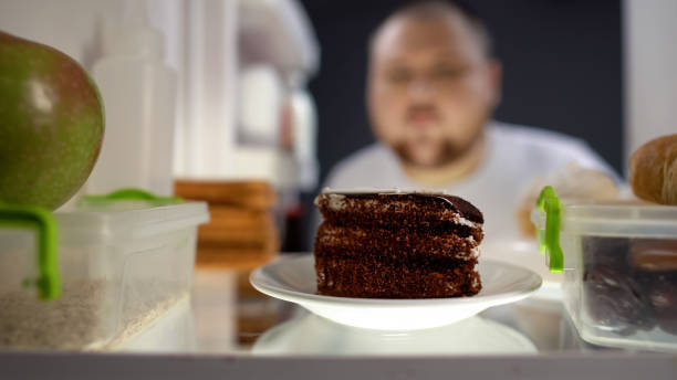 oversize man tar bit av kakan från kylskåp på natten, diabetesrisk, kalorier - cravings bildbanksfoton och bilder