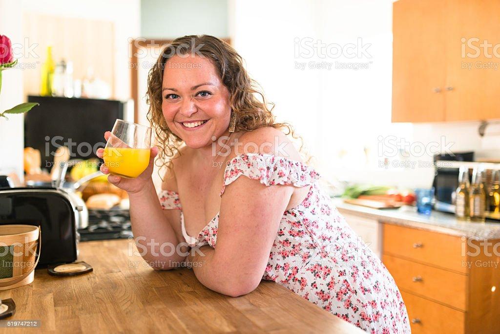 oversize woman drinking orange juice at home stock photo
