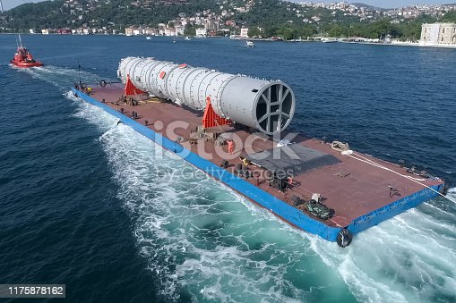 istock Oversized cargo transportation along the river, a distillation column on a barge floats to factory. 1175878162
