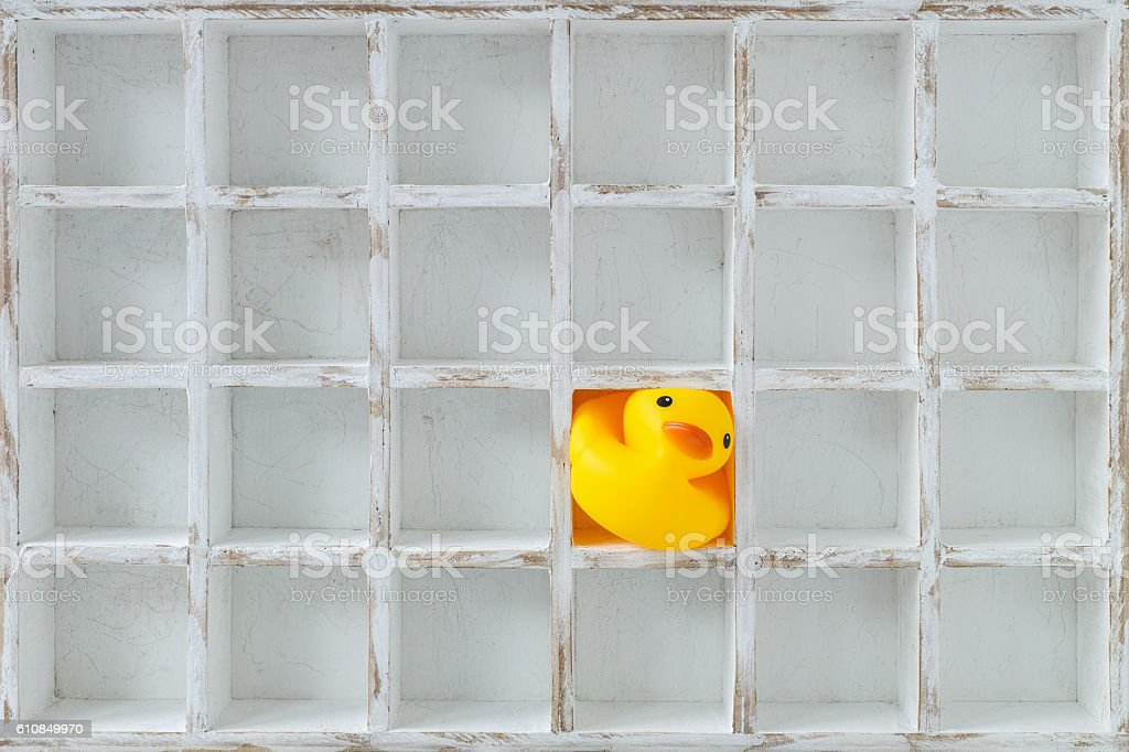 Oversized rubber duck in a compartment of many pigeon holes. stock photo