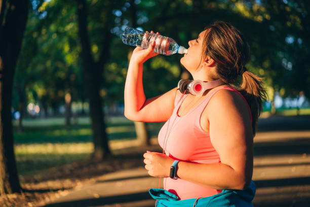 Oversized woman drinking water after running – zdjęcie