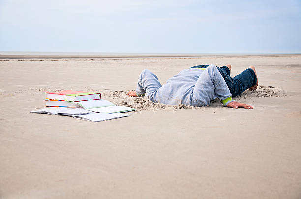 Overstrained child stucks head in sand Overstrained child stucks his head in the sand. In front of him are some school books. The picture symbolizes excessive demands, frustration and depression of children. Dark depressive sky. head in the sand stock pictures, royalty-free photos & images