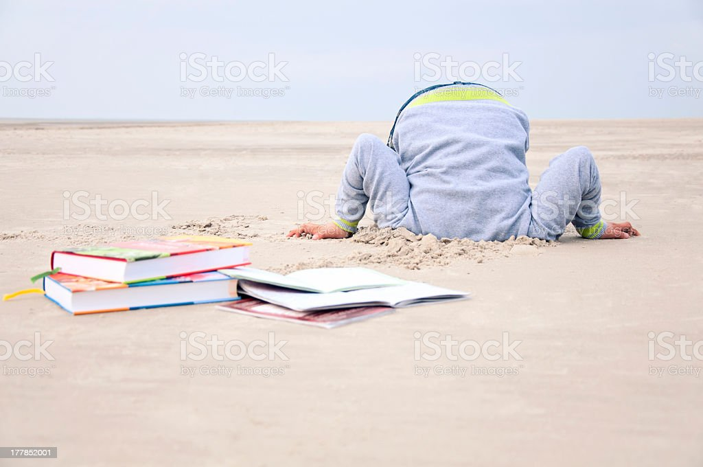 Overstrained child stucks head in sand royalty-free stock photo