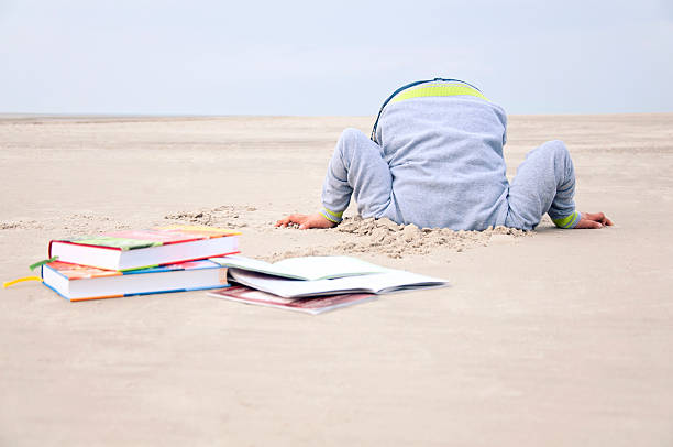 Overstrained child stucks head in sand Overstrained child stucks his head in the sand because of too much homework. Some books are lying in front of him. View from the front. Grey depressive sky.have a look at different variations:shoot in sunlight: head in the sand stock pictures, royalty-free photos & images