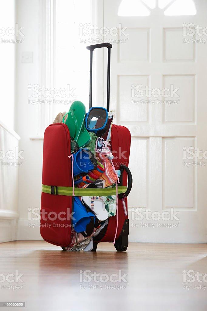 Overstuffed suitcase in hallway stock photo