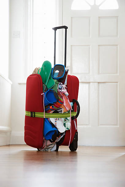 overstuffed suitcase in hallway - overflowing stock photos and pictures