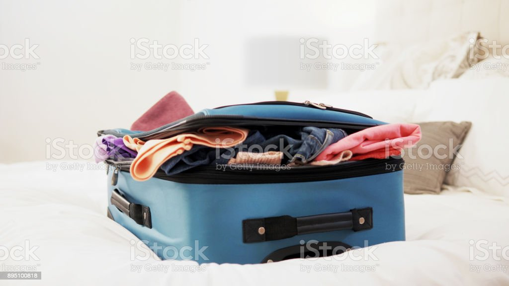 Overstuffed suitcase on top of bed. stock photo