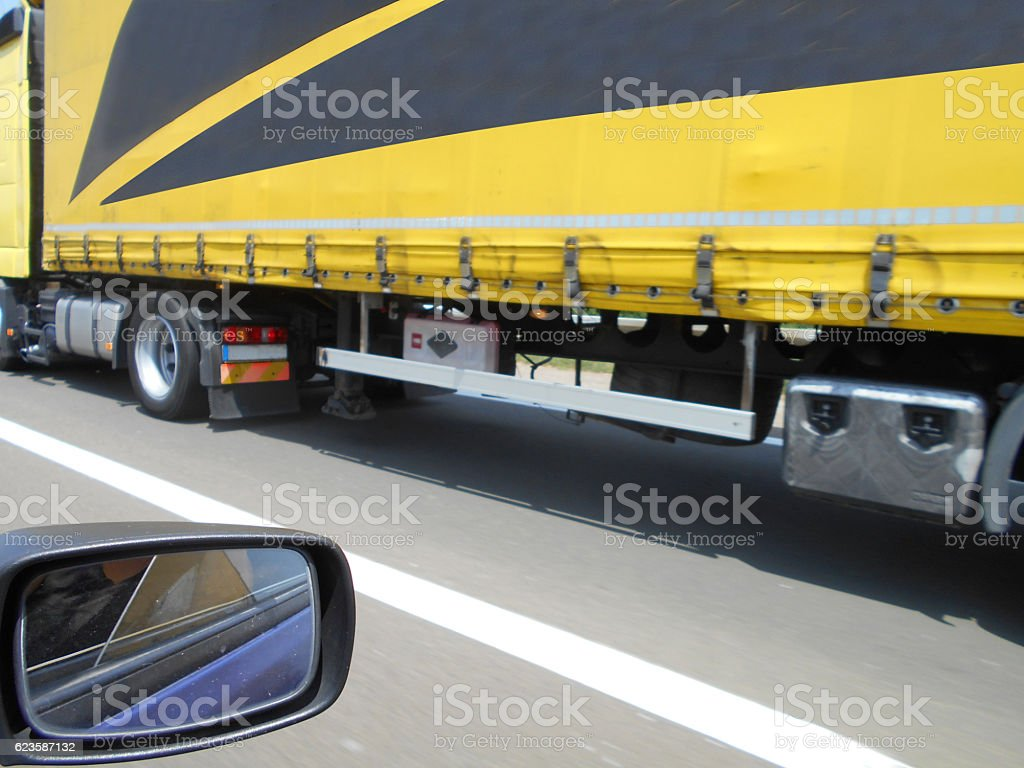 Overtaking a yellow truck on the highway stock photo