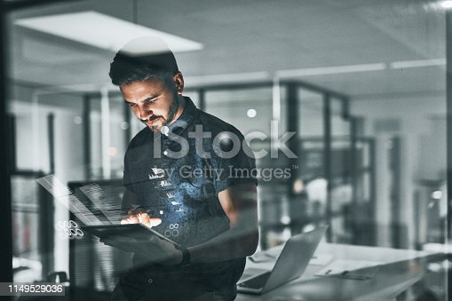 Cropped shot of a handsome young businessman working late in the office