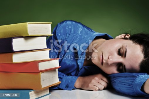 508126619istockphoto Overtired woman asleep next to pile of books 175512601