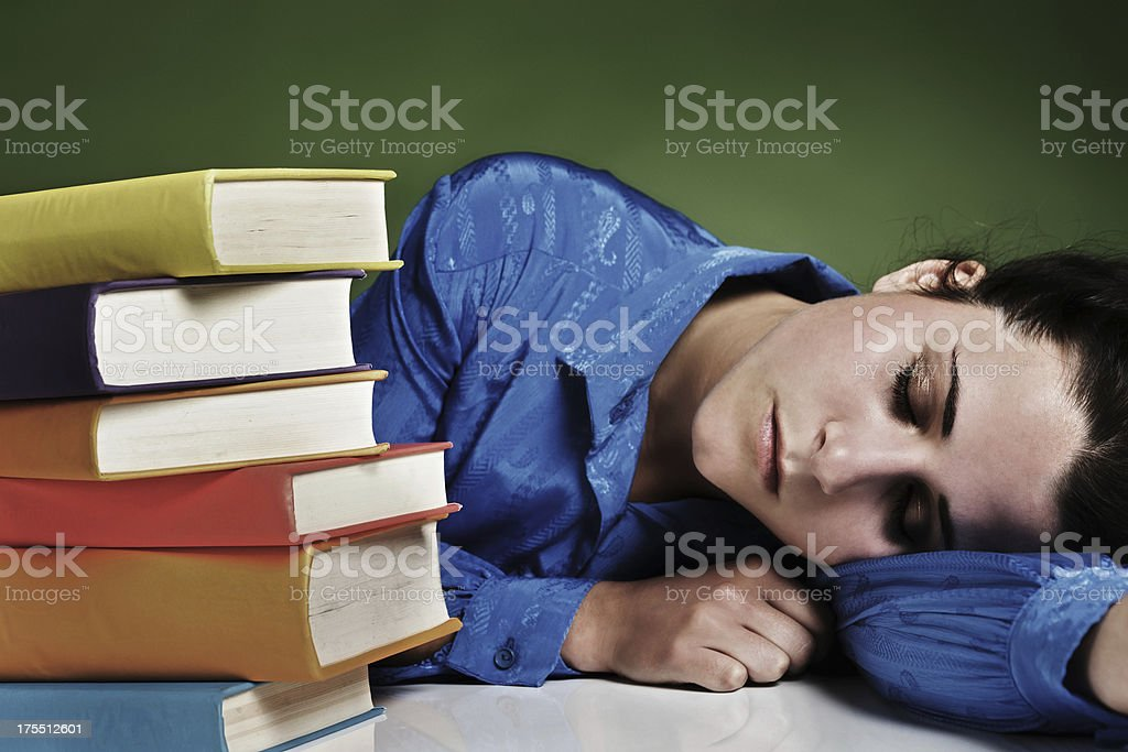 Overtired woman asleep next to pile of books stock photo