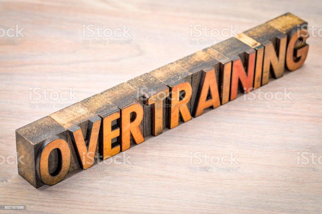 overtraining word abstract in wood type stock photo