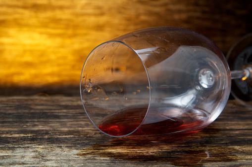 Overturned glass of wine on floor