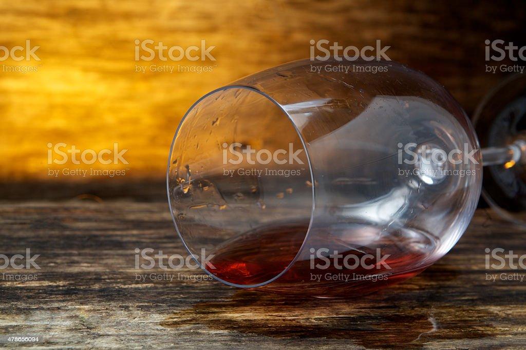 Overturned glass of wine on floor stock photo