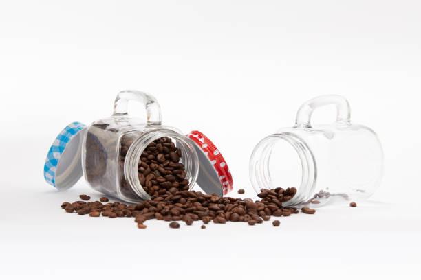 umgeworfene gläser voller kaffeebohnen auf weißem hintergrund - hausgemachter eiskaffee stock-fotos und bilder