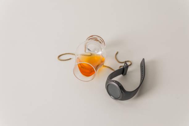 überdreht single malt whiskey-glas, auf weiß, mit goldkette und smartwatc - q q armbanduhr stock-fotos und bilder
