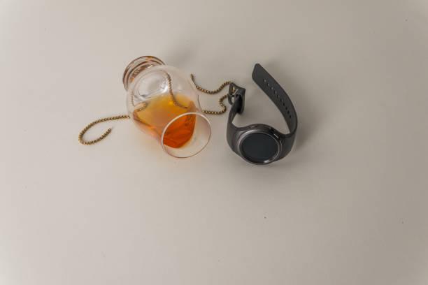 überdrehtes einzelnes malt whiskey-glas, auf weiß, mit goldkette und smartwatch - q q armbanduhr stock-fotos und bilder