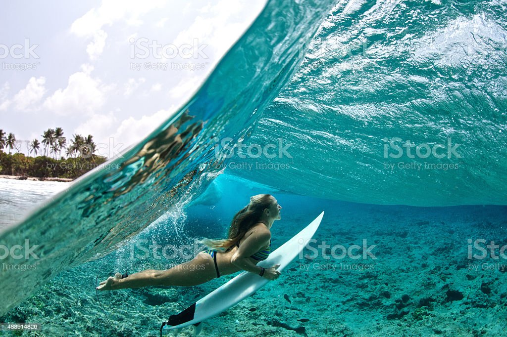 Over/under of surfer girl duck diving tropical waves stock photo