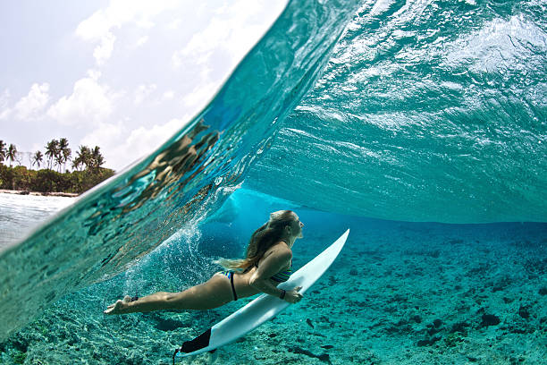 Over/under of surfer girl duck diving tropical waves​​​ foto