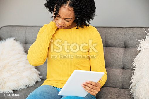 Young black woman holding a digital tablet, having pain in the neck area