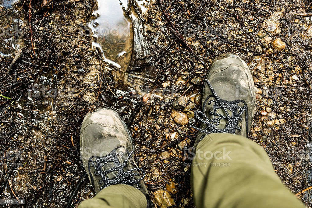 Overview close up of boots while hiking on trail stock photo