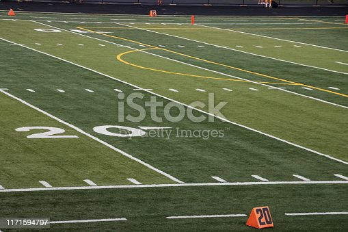 istock Overview of 20 yard line on football field of local high school with feet of people in background 1171594707