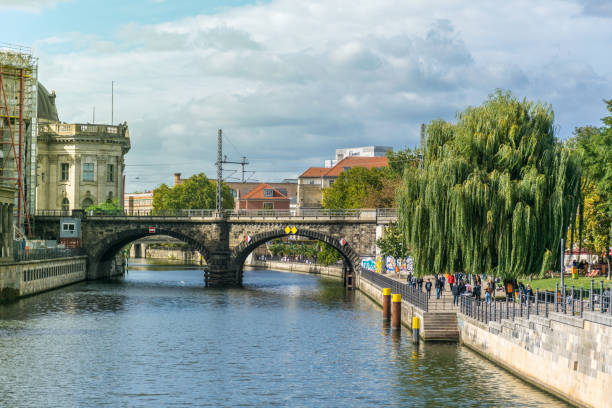 Überblick über eine Brücke über die Spree an einem sonnigen Tag mit vielen Besuchern im vielbefahrenen James Simon Park, in der Nähe des Berliner Doms und der Museumsinsel – Foto