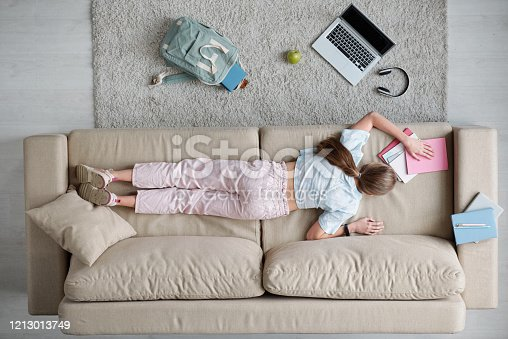 994789938 istock photo Overview of back of teenage girl lying on couch while doing homework 1213013749