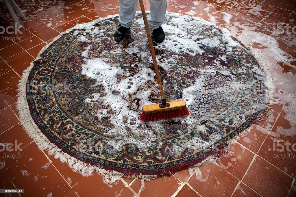 Overview of carpet cleaning worker scrubbing circular carpet royalty-free stock photo