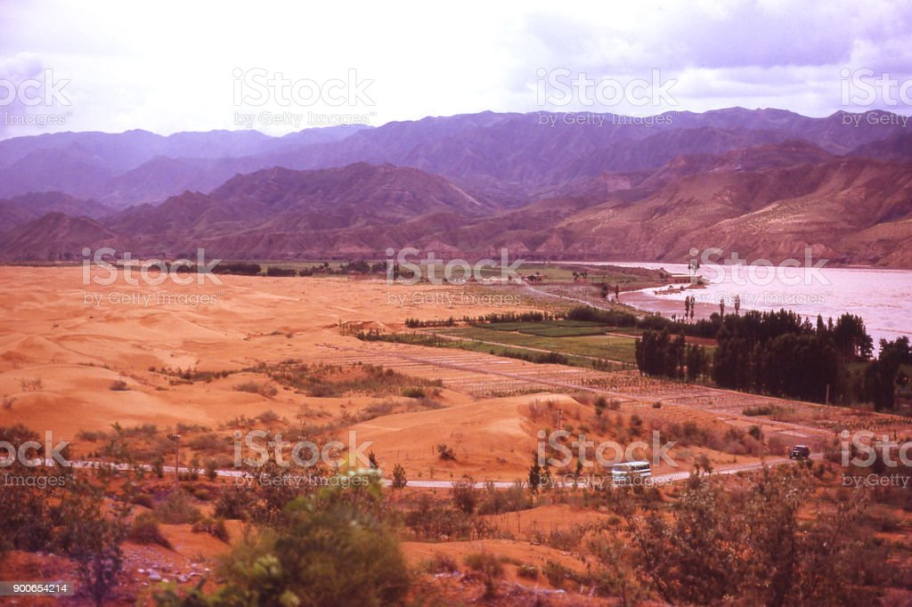 Overview of great bend in Yellow river where sand dunes invade from the Tonghu Desert near Zhongwei Ningxia China stock photo