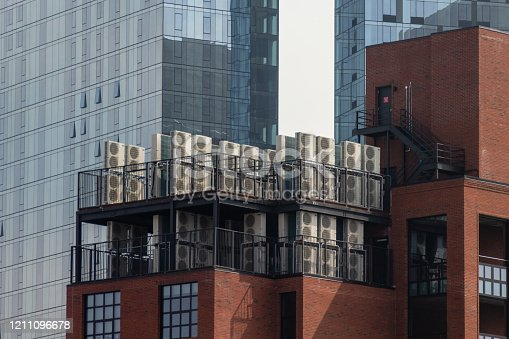 istock Overview of multiple air conditioning units on the roof of New York building 1211096678