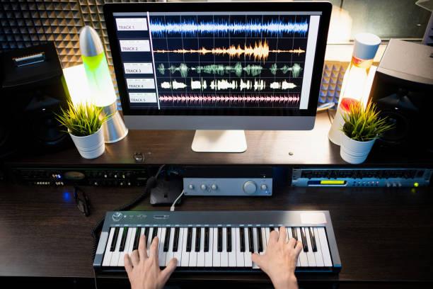 Visión general de los manos del músico sobre el teclado del piano y el monitor de la computadora en frente - foto de stock