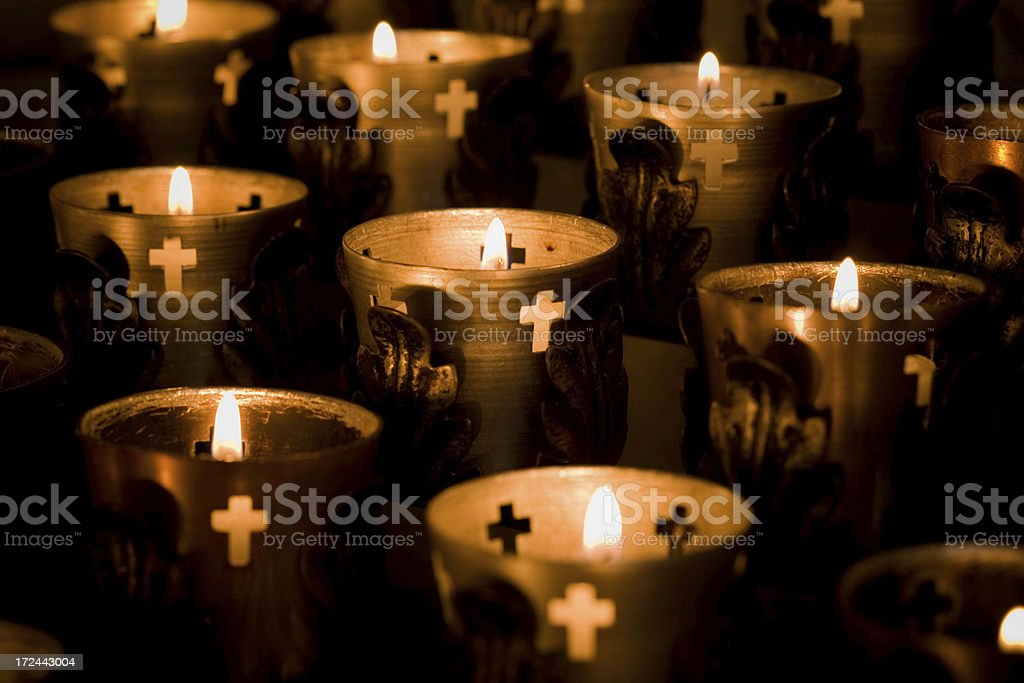 Overview of several prayer candles lit in dark room royalty-free stock photo