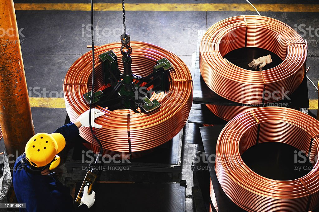 Overview of worker testing copper coils stock photo