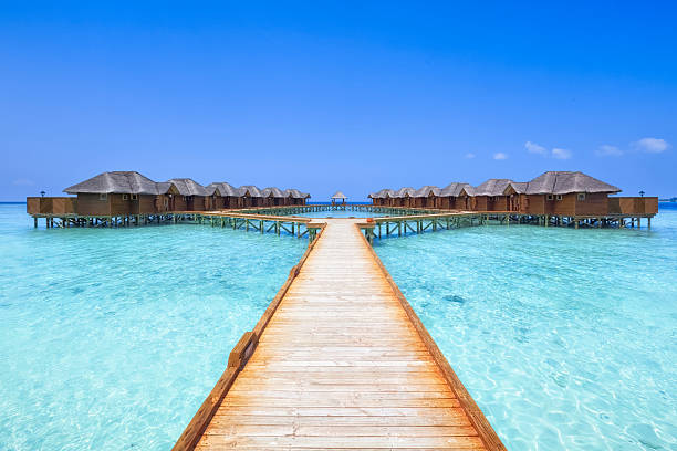Overwater Bungalows Boardwalk overwater bungalows boardwalk of the Maldives beach hut stock pictures, royalty-free photos & images