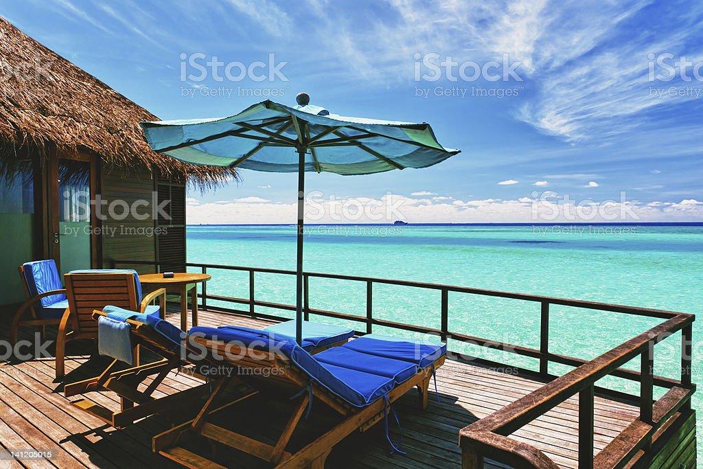 Overwater villa balcony overlooking tropical lagoon Overwater villa balcony overlooking green tropical lagoon Bungalow Stock Photo