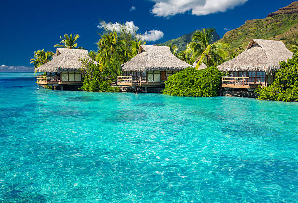 Overwater villas in lagoon of Moorea Island Overwater villas in tropical lagoon of Moorea Island bungalow stock pictures, royalty-free photos & images