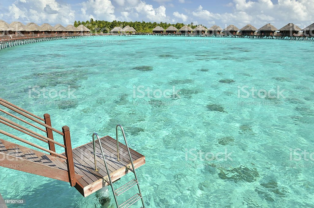 Overwater villas with steps into the green lagoon stock photo
