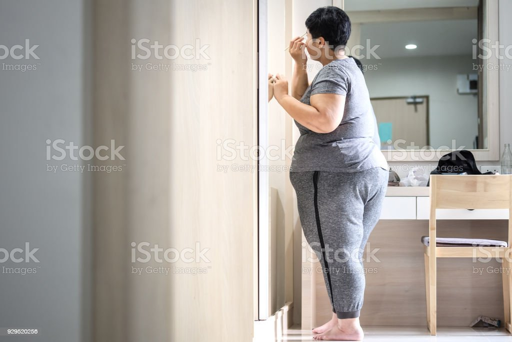 Overweight Asian women standing Makeup in front of the mirror stock photo