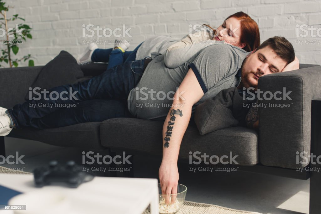 overweight boyfriend and girlfriend sleeping on sofa at home with...