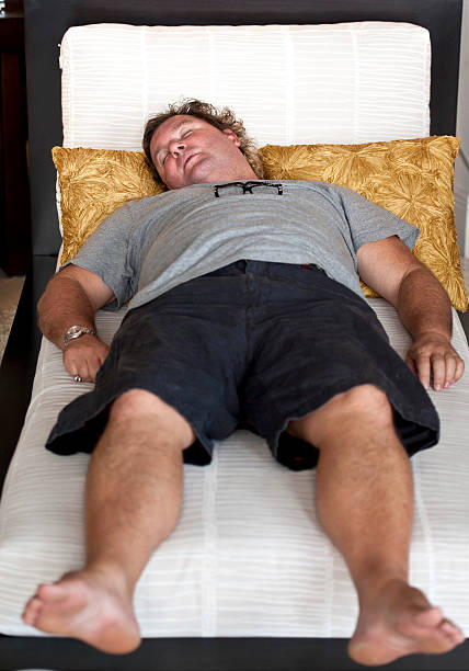 sovrappeso caucasico maturo uomo di dormire su un divano - divano procrastinazione foto e immagini stock