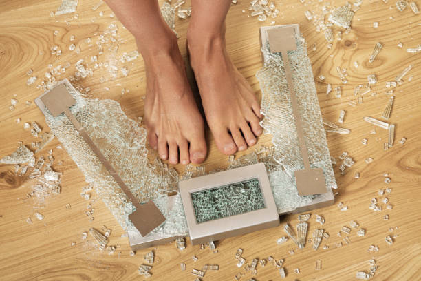 Overweight concept. Female feet and cracked glass weighing scale. stock photo