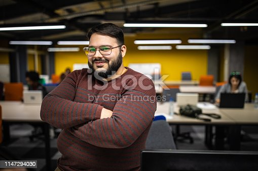 Overweight businessman sitting on his desk in modern office space, with crossed arms smiling and looking at camera